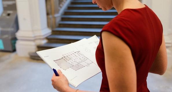 female engineer holding floorplan with mistakes on it
